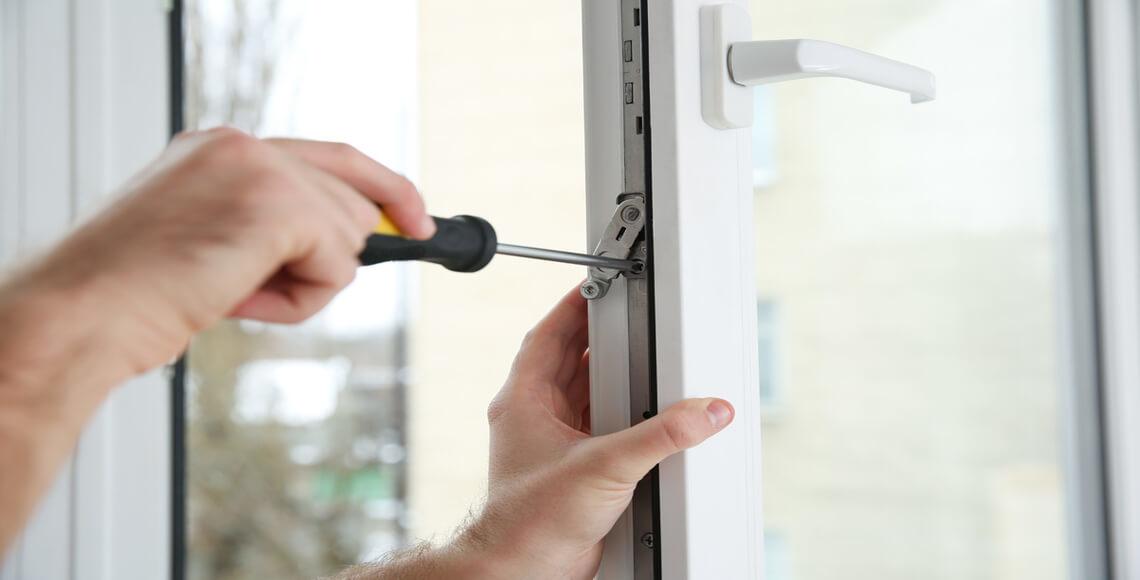 persona che cerca di riparare finestra bloccata con cacciavite