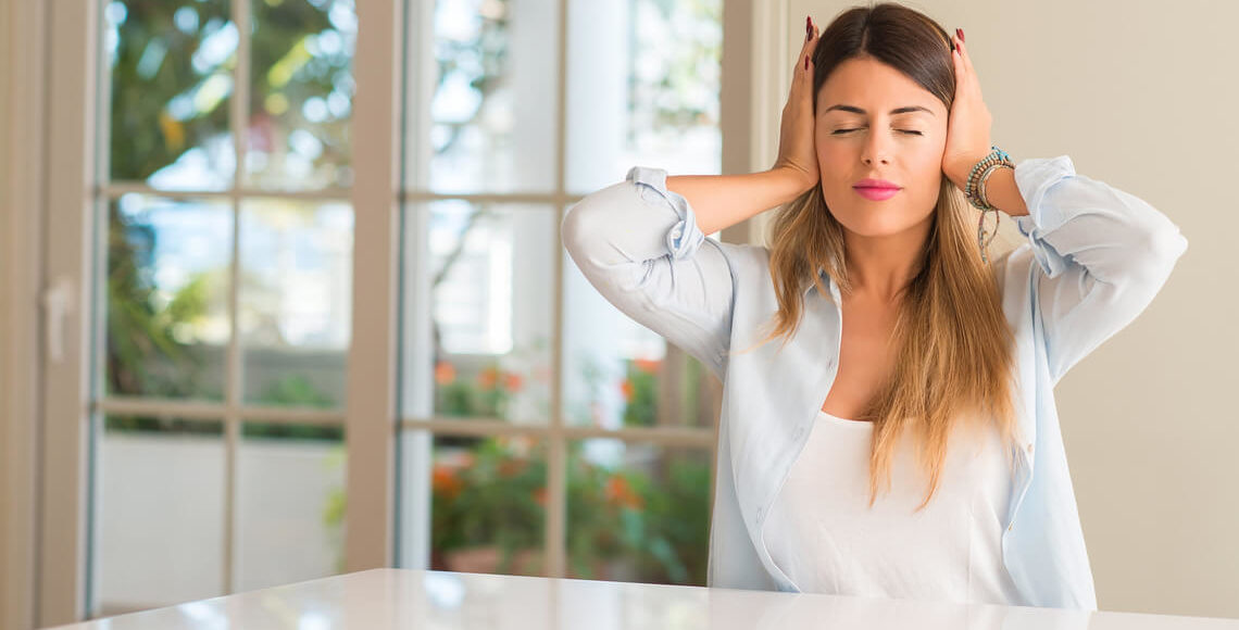donna che si tappa le orecchie vicino finestra senza isolamento acustico