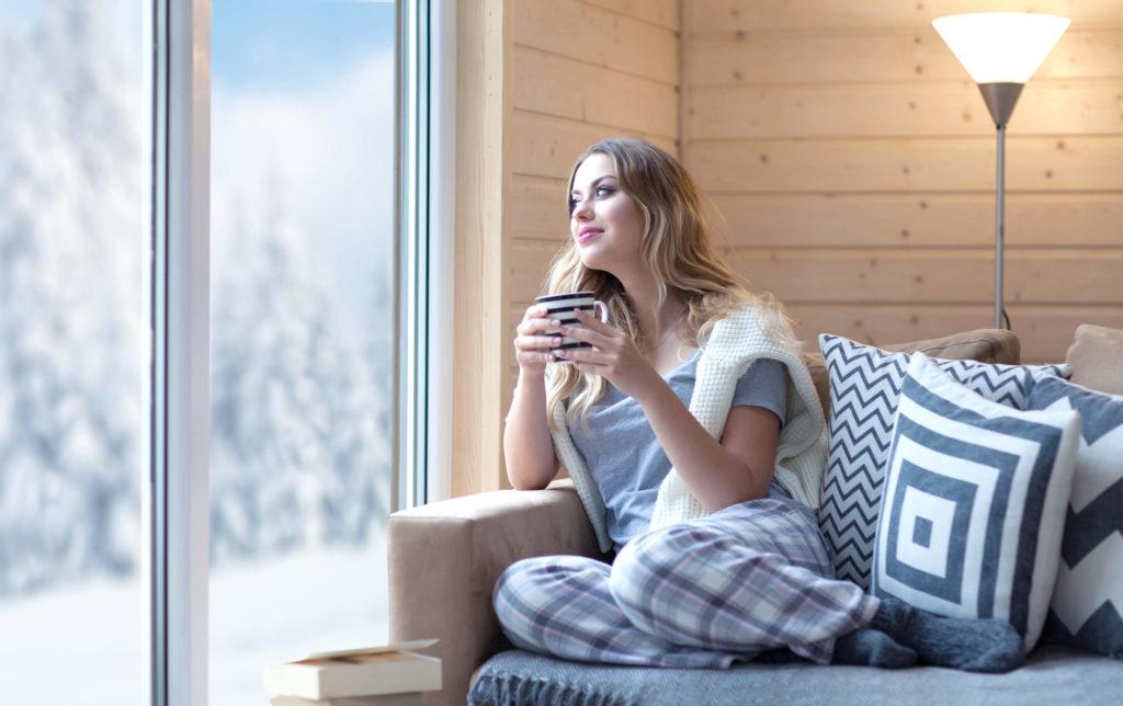 ragazza beve caffè vicino finestre bassa trasmittanza termica