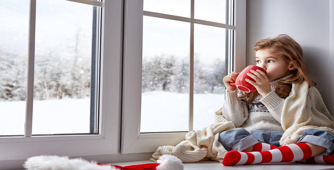 bambina che guarda fuori dalla finestra grazie al comfort abitativo